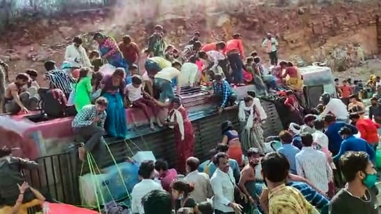 Migrants deboard an overcrowded bus after it overturned and lost balance in Gwalior district on Tuesday.(PTI)