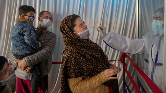 A health worker takes a nasal swab sample of a Kashmiri woman to test for COVID-19 as her family members watch in Srinagar, Indian-controlled Kashmir, Thursday, April 15, 2021. India's two largest cities imposed stringent restrictions on movement and one planned to use hotels and banquet halls to treat coronavirus patients amid a devastating surge that is straining a fragile health system. (AP Photo/ Dar Yasin)(AP)