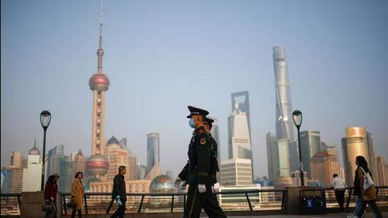 Police officers walk at the Bund, in front of Lujiazui financial district of Pudong in Shanghai, China. (REUTERS)