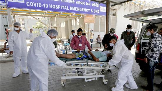 Health workers carry a Covid-19 patient to the OPD ward of a hospital, as cases surge in record numbers across the country, in Ahmedabad. (PTI)