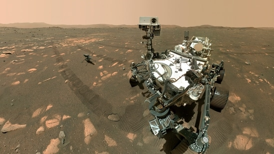 NASA's Perseverance Mars rover, foreground, and the Ingenuity helicopter about 13 feet (3.9 meters) behind. (AP)