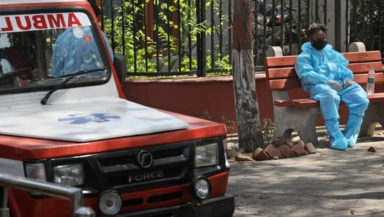 A health worker sits on a bench after helping cremating victims of coronavirus, in New Delhi.