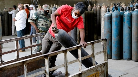 Workers load oxygen cylinders at a charging station on Friday.(AP File Photo )