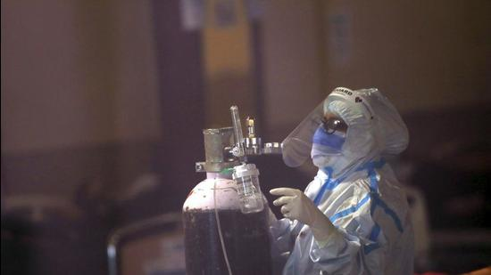 File photo: A health worker fixes an oxygen cylinder for a Covid-19 patient. (AP)