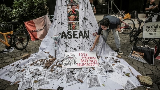 A woman prepares a placard out of crossed out portraits of Myanmar's junta chief Senior General Min Aung Hlaing during protest against the military coup in Myanmar.(Reuters)