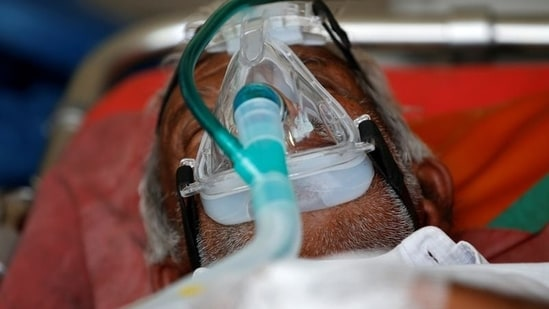 A patient wearing an oxygen mask is seen inside an ambulance waiting to enter a Covid-19 hospital.(Reuters)