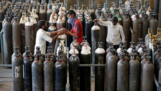 People carry oxygen cylinders after refilling them in a factory, amidst the spread of the coronavirus disease (COVID-19) in Ahmedabad. (Reuters)