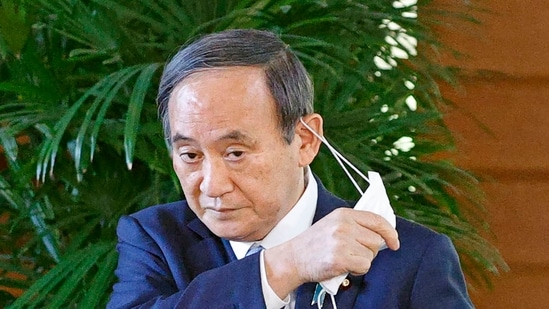 Japanese Prime Minister Yoshihide Suga takes off his face mask before speaking to reporters at his office in Tokyo.(AP)