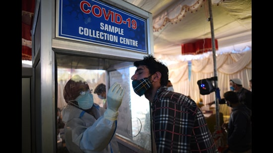 A health worker collects a swab sample from a man for Covid test in Srinagar. (Waseem Andrabi.HT)