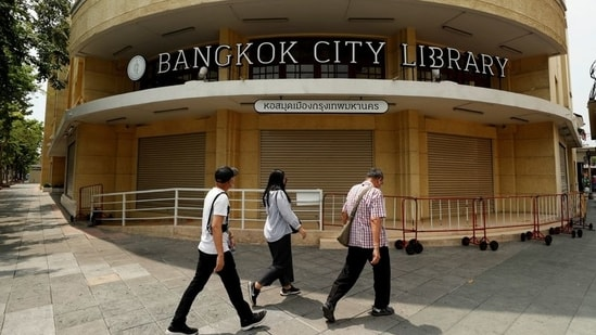People walk past the closed city library as the country struggles with a third wave of infections of the coronavirus disease (Covid-19) outbreak in Bangkok Thailand.(Reuters)
