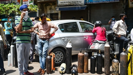 People wait to refill empty oxygen cylinders, at Bhogal Jangpura, in New Delhi, India, on Tuesday, April 27, 2021. (Photo by Amal KS/ Hindustan Times)