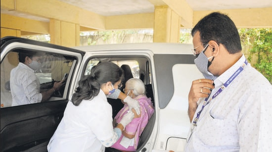 An elderly woman gets vaccinated in the car by hospital staff at Bindumadhav Balasaheb Thackeray hospital, Kothrud on Monday. Many hospitals have taken the initiative to inoculate beneficiaries outside the stationary centres. (HT PHOTO)