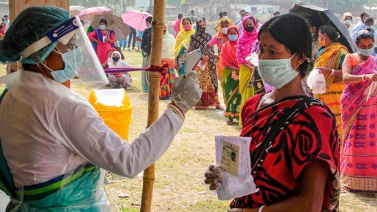 A health worker sanitises voters as they wait in queues to cast votes at a polling station during the 7th phase of West Bengal Assembly elections at a village near Balurghat in South Dinajpur district, Monday, April 26, 2021. (PTI)