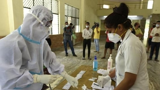 A health worker in PPE kit conducts rapid antigen Covid-19 tests, at Sukhrali Village Community Centre, in Gurugram.(Parveen Kumar/ HT file photo)