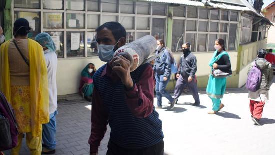File photo: A man carrying an oxygen cylinder at IGMC hospital, Shimla.   (Deepak Sansta / Hindustan Times)
