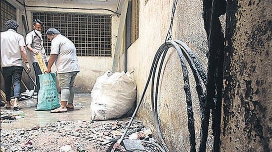 Workers clean the parking lot at the Kamala Nehru hospital on April 26, 2021, after a minor fire broke out. (KALPESH NUKTE/HT)