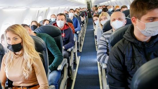Passengers wear protective face masks onboard a plane (Reuters File Photo )