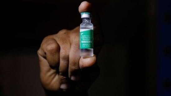 A man displays a vial f AstraZeneca's COVISHIELD vaccine. (REUTERS)