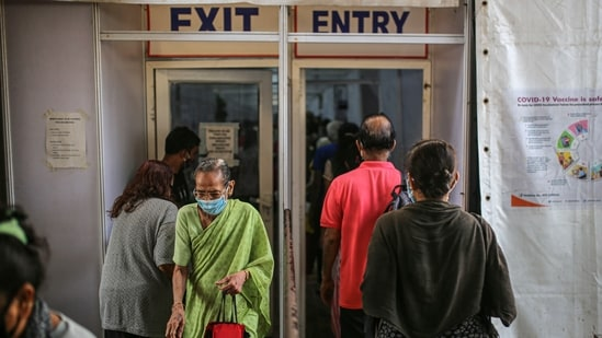 People enter and exit a Covid-19 vaccination center at the BKC NESCO jumbo Covid centre in the Goregaon suburb of Mumbai.(Bloomberg Photo)