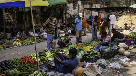 Customers wear protective masks and face coverings while shopping for vegetables from street vendors at a market in the Azadgarh area of Kolkata, India.(Bloomberg)