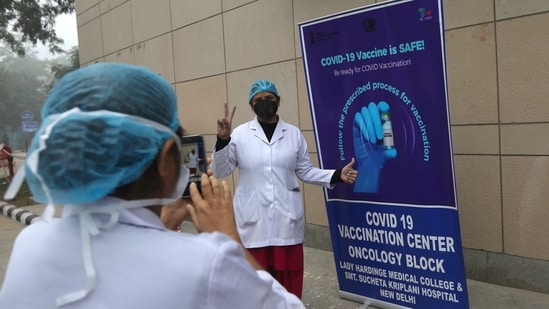 A health worker gestures as she gets her photograph taken next to a Covid-19 vaccination banner at a hospital in New Delhi.(AP)