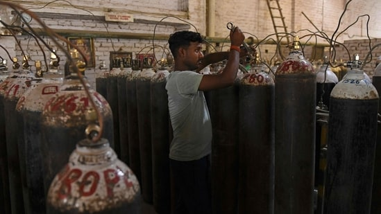 Workers are seen sorting oxygen cylinders that are being used for Covid-19 coronavirus patients before dispatching them to hospitals at a facility on the outskirts of Amritsar on April 28, 2021. (AFP)