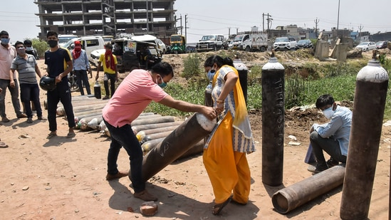 A family member of a Covid-19 patient carries an oxygen cylinder for refilling outside a filling centre, in Patna, Wednesday.(PTI)
