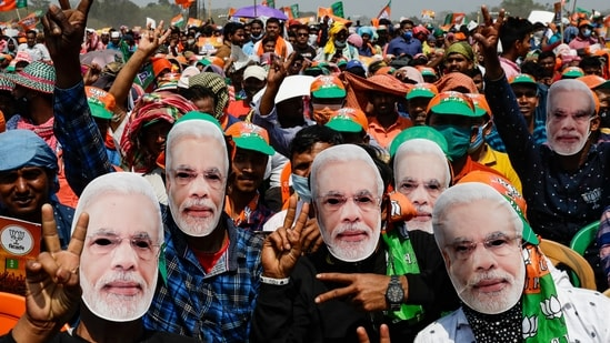 Bharatiya Janata Party (BJP) supporters wear masks of Prime Minister Narendra Modi as they gather for a rally addressed by Modi ahead of West Bengal state elections in Kolkata, India.(AP)