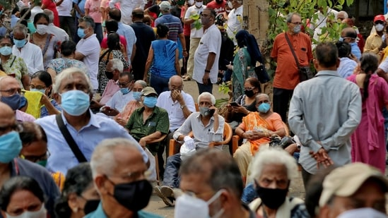People wearing protective face masks wait to receive a vaccine for the coronavirus disease (Covid-19) at a vaccination centre in Mumbai.(Reuters Photo )