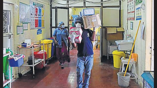 A medical helper carries medical goods to the isolation ward of the Ahmedabad Civil Hospital, in Ahmedabad. (HT archive)