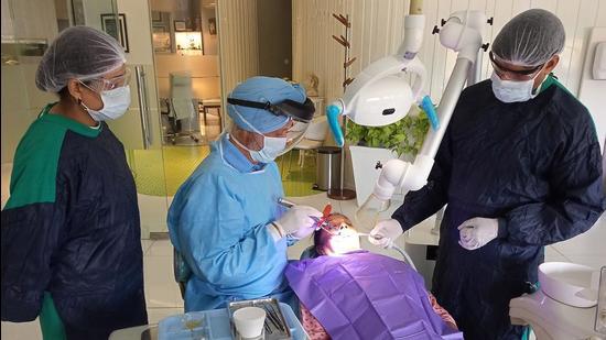 Dr JS Batth conducting a dental procedure at his clinic in Sector 5, Panchkula. (Sant Arora/HT)