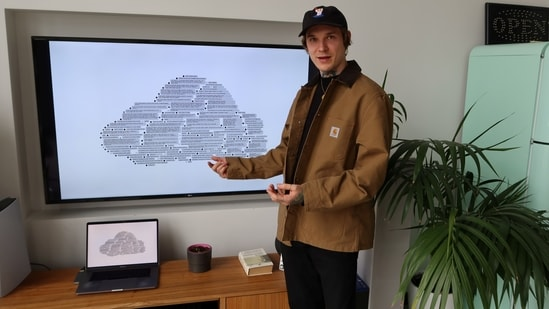 Erikas Malisauskas, a designer, stands next to Hate Speech Cloud, his digital collage of homophobic messages that were sent to a member of parliament who champions gay rights causes, in his apartment in Vilnius, Lithuania April 27, 2021. (REUTERS)