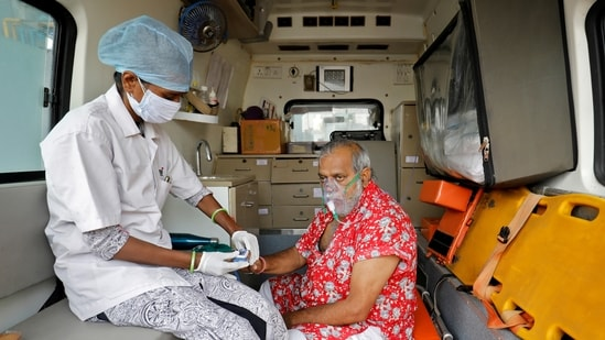 A paramedic uses an oximeter to check the oxygen level of a patient inside an ambulance while waiting to enter a Covid-19 hospital.(Reuters)