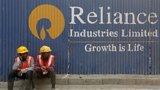 Labourers rest in front of an advertisement of Reliance Industries Limited at a construction site in Mumbai.(REUTERS)