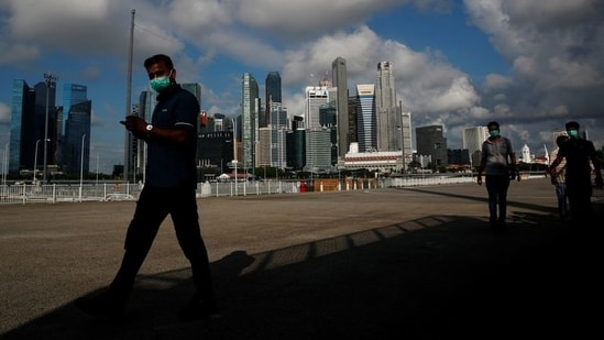 Essential workers wearing face masks walk past the skyline of the central business district outside a regional screening center amid the coronavirus disease (Covid-19) outbreak in Singapore.(Reuters)