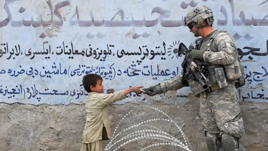 In this file photo taken on February 20, 2010, a US soldier from 4th Infantry Division 4 Brigade Alpha Company presents a gift to an Afghan child during a patrol at Khogyani in Nangarhar. (Photo by KIM JAE-HWAN / AFP)