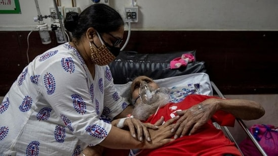A man suffering from the coronavirus disease (Covid-19) is comforted by his daughter as he receives treatment inside the casualty ward at a hospital.(Reuters)