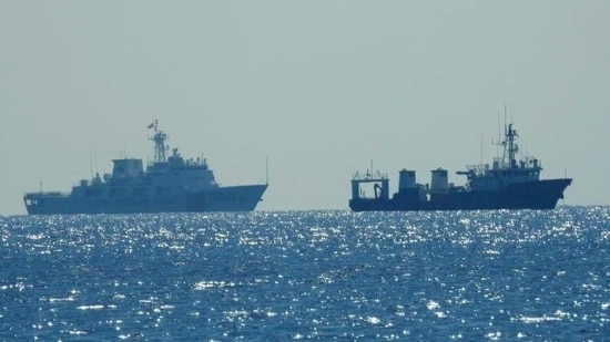 A Chinese Coast Guard patrol ship (L) is seen near an unidentified vessel at South China Sea. (REUTERS)