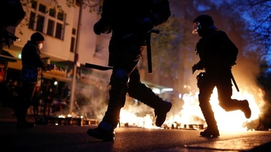 Police officers run past a fire during a left-wing May Day demonstration, as the spread of Covid-19 continues in Berlin, Germany.(REUTERS)