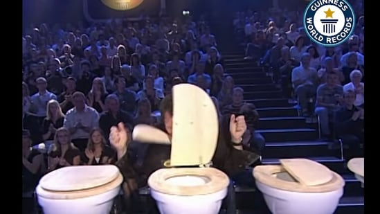 The image shows of the participants competing for the record of most toilet seats broken by head in one minute.(Facebook/@@GuinnessWorldRecords)