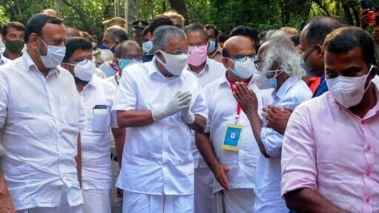 Kerala chief minister Pinarayi Vijayan greets other leaders and supporters as he arrives at a vote counting center following LDF's victory, in Kannur, Kerala.