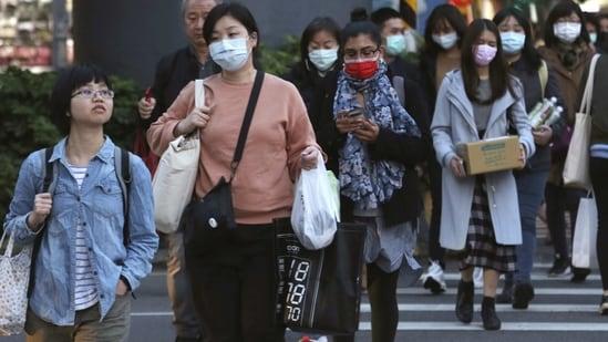 People wear face masks to help curb the spread of the coronavirus in Taipei, Taiwan.(AP Photo)