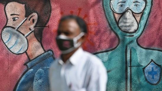 A pedestrian walks past a wall mural depicting frontline Covid-19 coronavirus warriors wearing face masks along a road.(AFP)