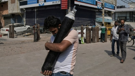 A man walks carrying a refilled cylinder as family members of Covid-19 patients wait in queue to refill their oxygen cylinders at Mayapuri area in New Delhi, India.(AP)