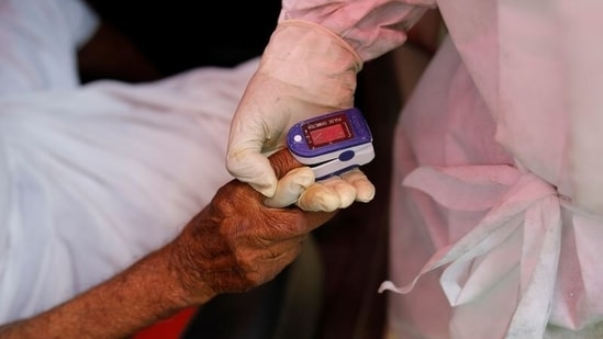 A volunteer uses an oximeter to check the oxygen level of a man before providing oxygen support for free, amidst the spread of coronavirus disease (COVID-19), outside a Gurudwara (Sikh temple) in Ghaziabad, India, April 30, 2021. (REUTERS)