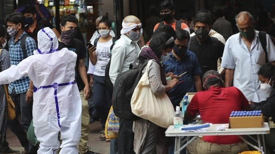 Health worker directs arriving passengers towards Covid-19 testing counter outside a train station in Bengaluru.(AP file photo)