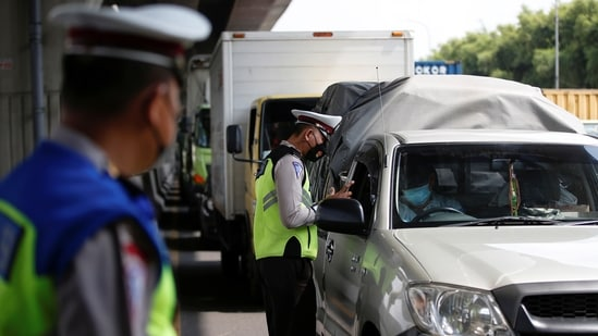 Police officer inspects a car at a checkpoint on the first day of a national travel ban as Indonesia halts sea, land, air, and rail travel.(Reuters)