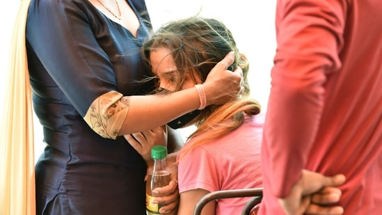 """A girl being consoled by a relative at an """"Oxygen langar"""" for Covid-19 patients, by Gurdwara Damdama Sahib in New Delhi, India.(Ajay Aggarwal /HT PHOTO)"""