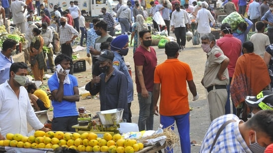 The sabzi mandi in Chandigarh Sector 26 continues to remain crowded despite the administrations restrictions imposed from Tuesday. Many vendors could be seen wearing their masks improperly.(Keshav Singh/Hindustan Times)