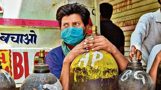 A man waits to refill oxygen cylinders for Covid-19 patients at a centre in New Delhi on Friday.(AFP)